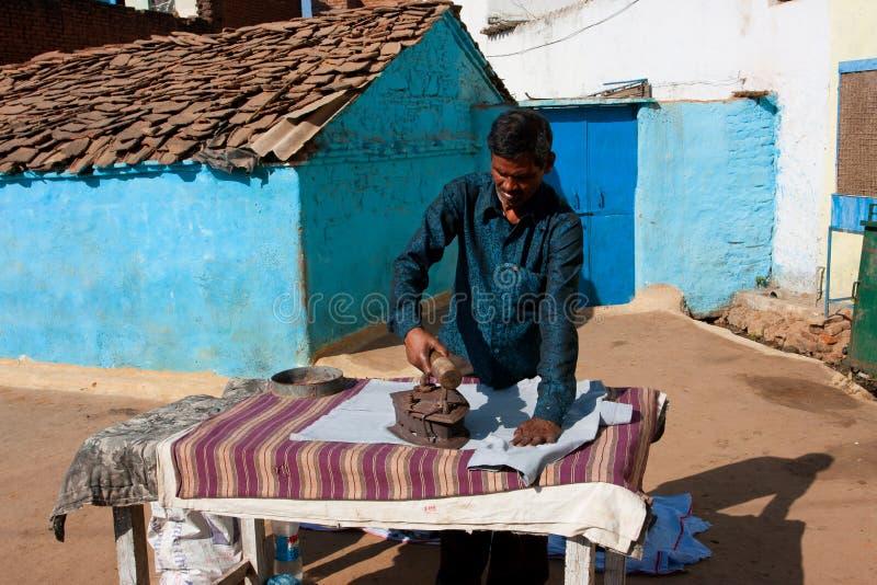 Азиатский человек утюжит одежды утюгом угля напольным стоковая фотография
