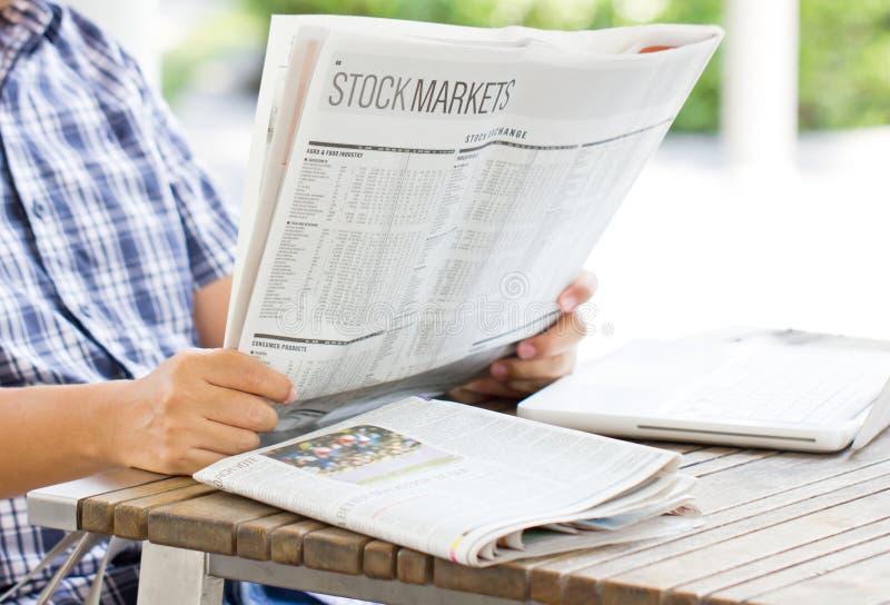Азиатский человек читая финансовую газету. стоковое фото