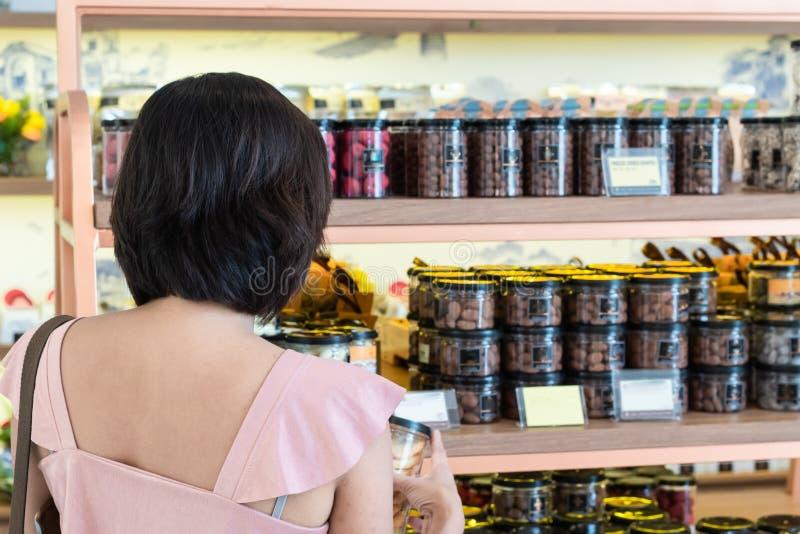 Азиатский шоколад покупки женщин в магазине стоковое изображение