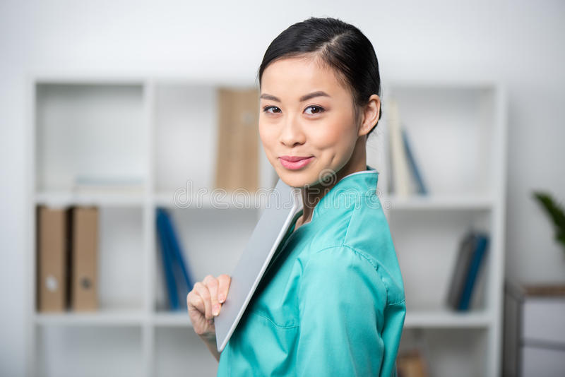 Азиатский internist используя цифровую таблетку в профессиональной клинике стоковое фото