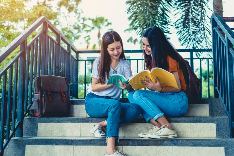 2 азиатских девушки красоты читая и обучая книги для заключительного экзамена совместно Студент усмехаясь и сидя на лестнице E стоковое изображение