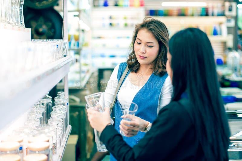 2 азиатских женщины выбирая и покупая стекла в sho изделий кухни стоковое изображение