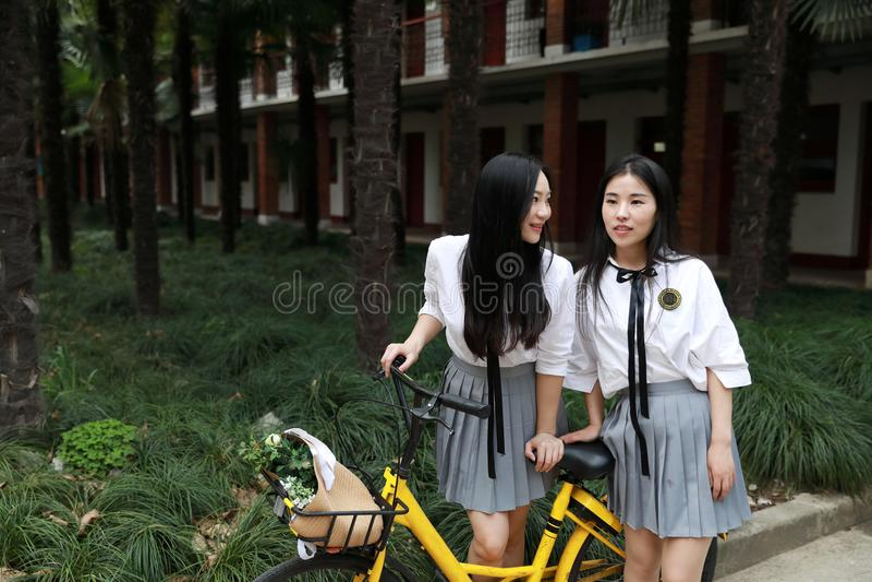 2 азиатских китайских счастливых милых прелестных симпатичных друз bestie студентов едут велосипед делят желтым цветом, который в стоковая фотография