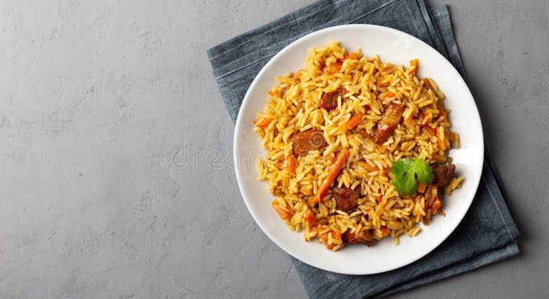 Азиатское блюдо - pilaf от от риса, овощей и мяса в плите на серой предпосылке стоковые фото