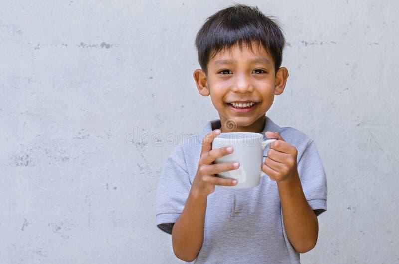 Азиатское владение ребенка кружка воды подготавливает выпить стоковые фото