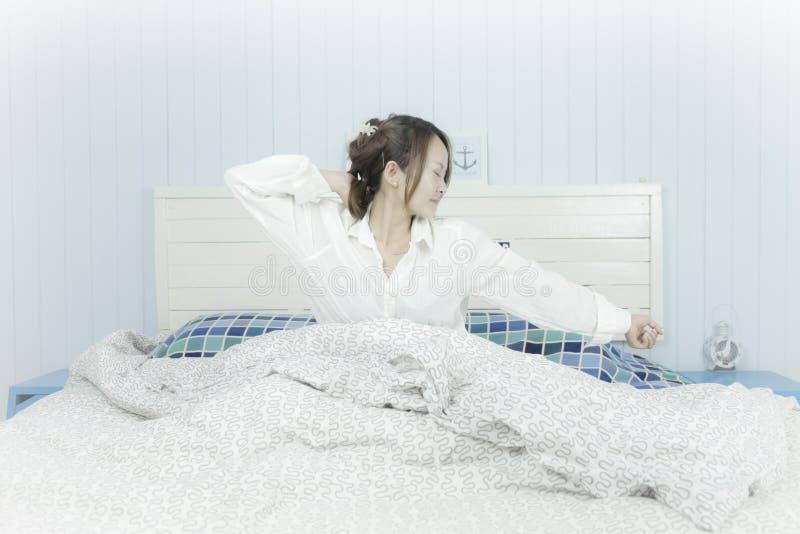 азиатское красивейшее слушая нот к женщине Слушая концепция наушников музыки Привлекательная азиатская женщина просыпаясь на кров стоковые фото