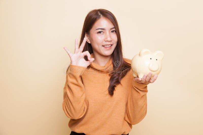 Азиатское О'КЕЙ выставки женщины с банком монетки свиньи стоковое изображение