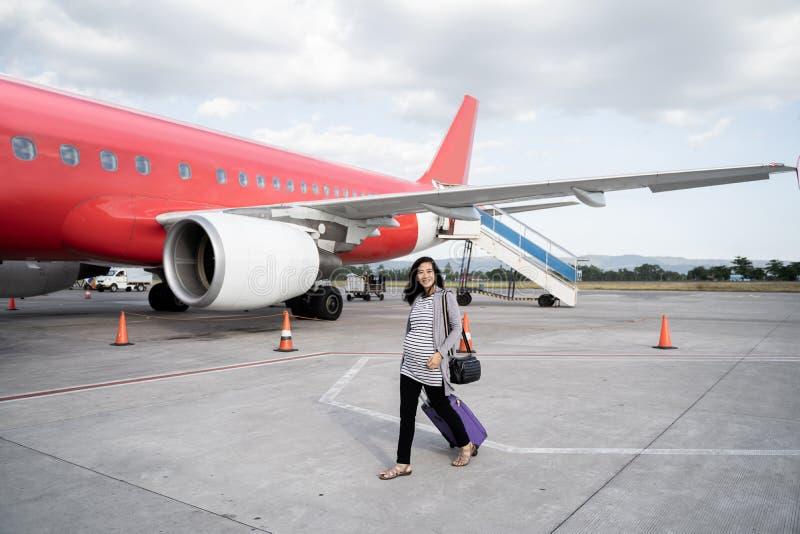Азиатское положение беременной женщины вытягивая чемодан стоковое фото