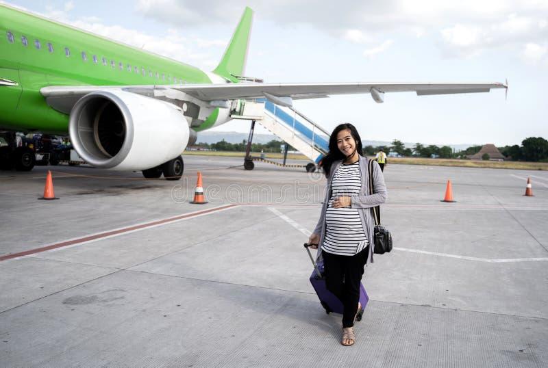 Азиатское положение беременной женщины вытягивая чемодан стоковое фото rf