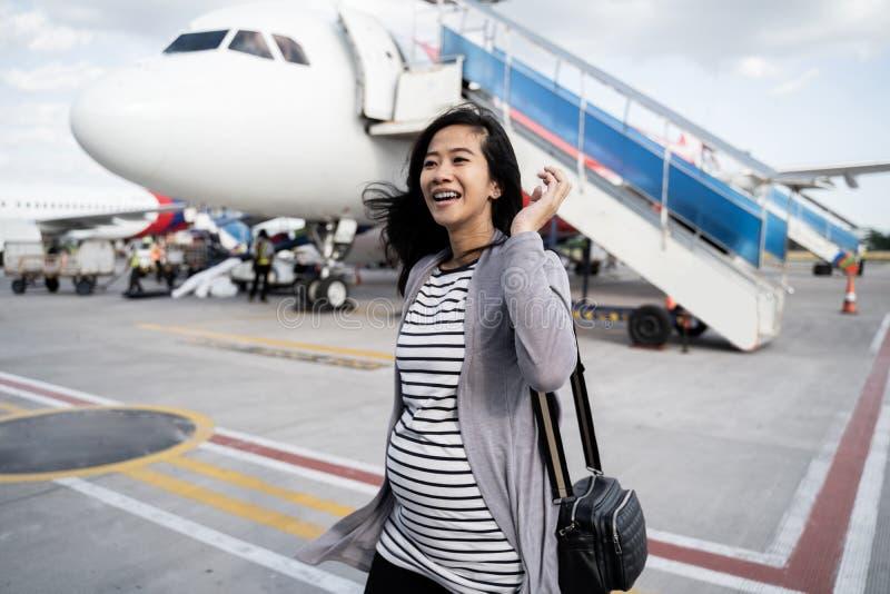 Азиатское положение беременной женщины вытягивая чемодан стоковые изображения