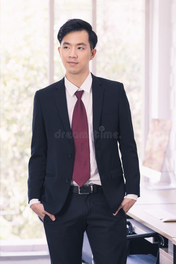 Азиатское положение бизнесмена и представлять в офисе стоковая фотография rf