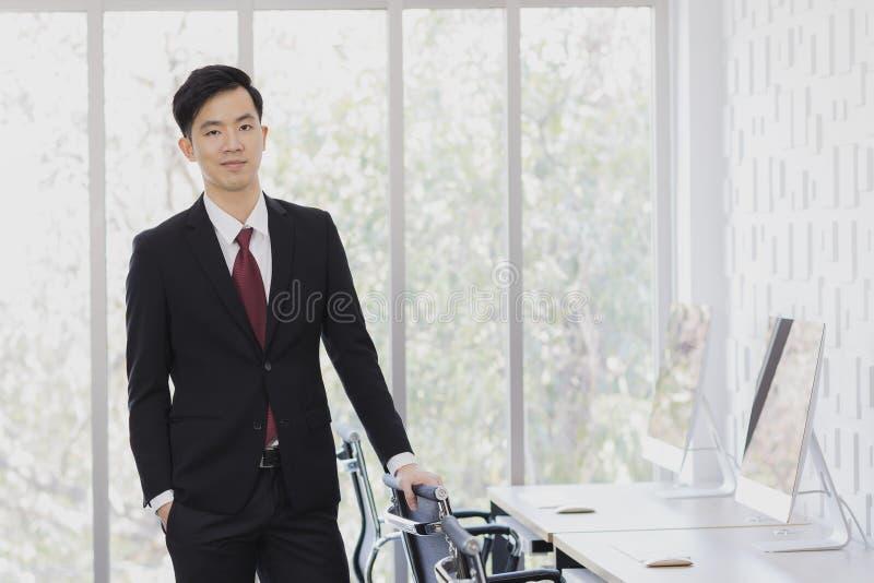 Азиатское положение бизнесмена и представлять в офисе стоковое изображение rf