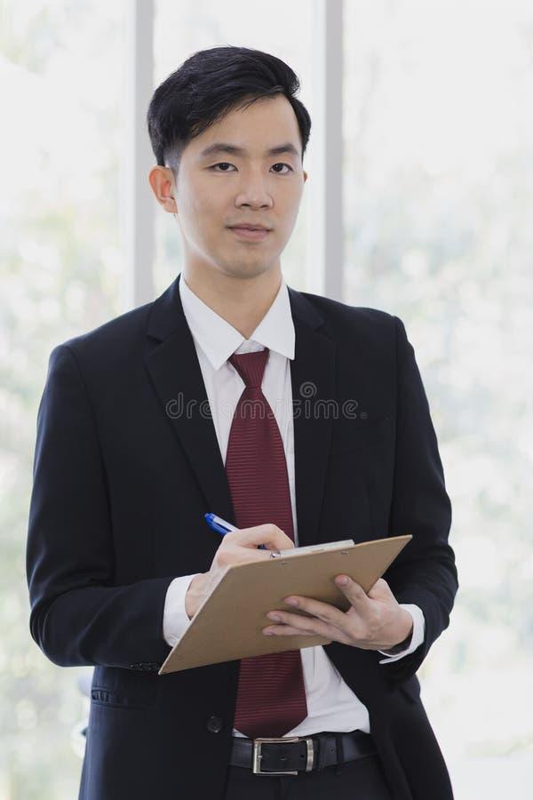 Азиатское положение бизнесмена и представлять в офисе стоковые изображения
