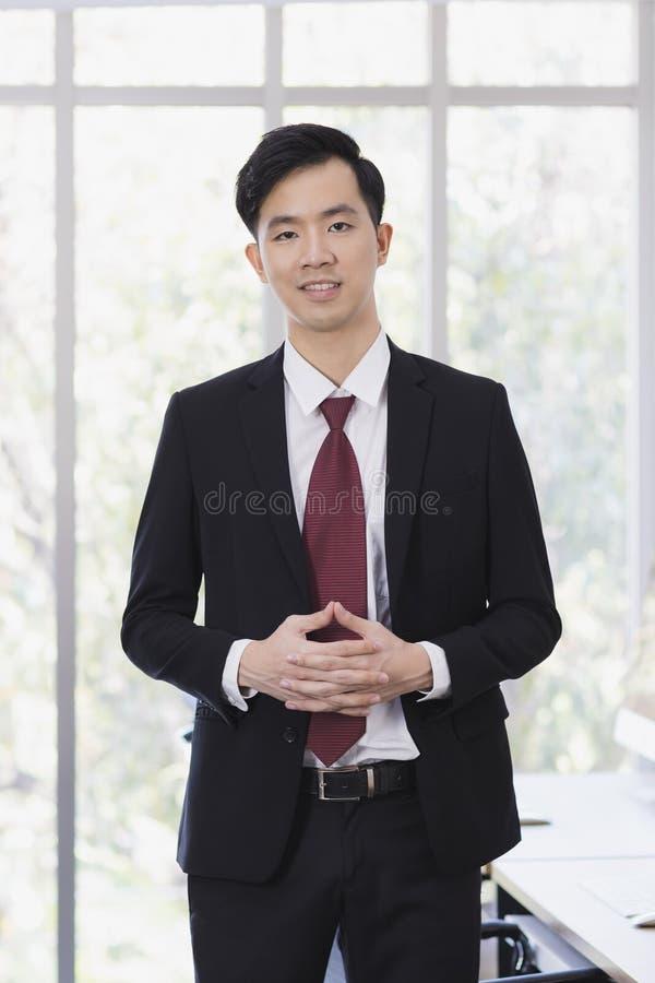 Азиатское положение бизнесмена и представлять в офисе стоковое изображение