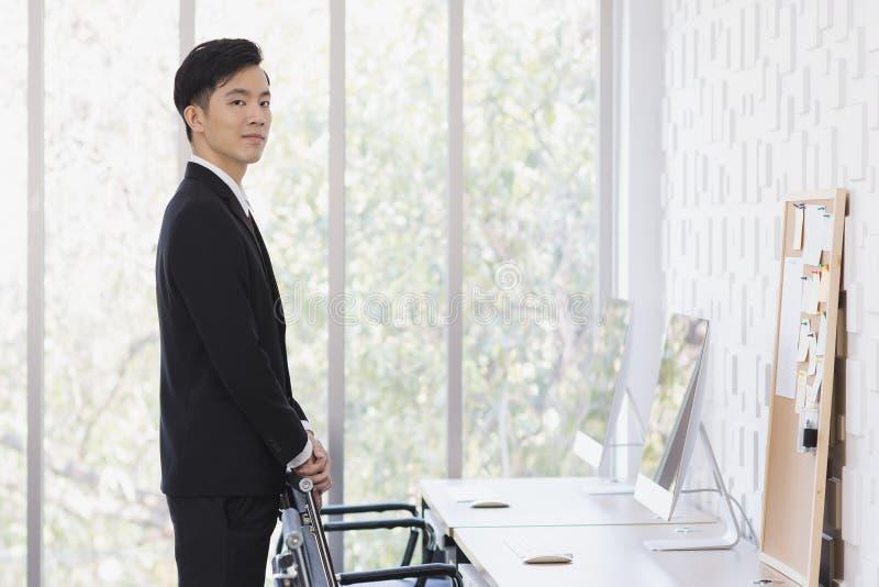Азиатское положение бизнесмена и представлять в офисе стоковые изображения rf