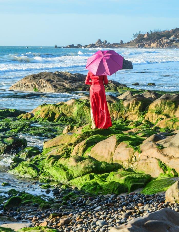 Азиатское положение женщины на пляже стоковые фотографии rf