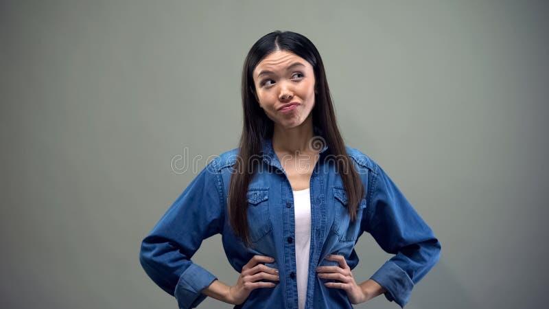 Азиатское положение женщины на серой предпосылке, смущаясь что, который нужно выбрать, решение стоковые изображения rf