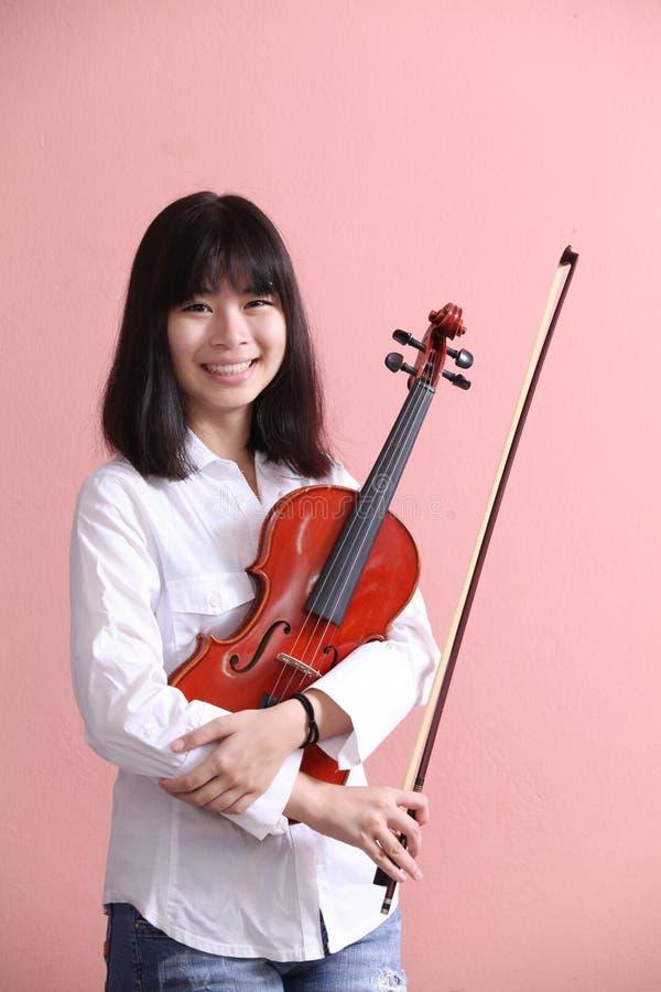 Азиатское предназначенное для подростков с улыбкой скрипки стоковые изображения