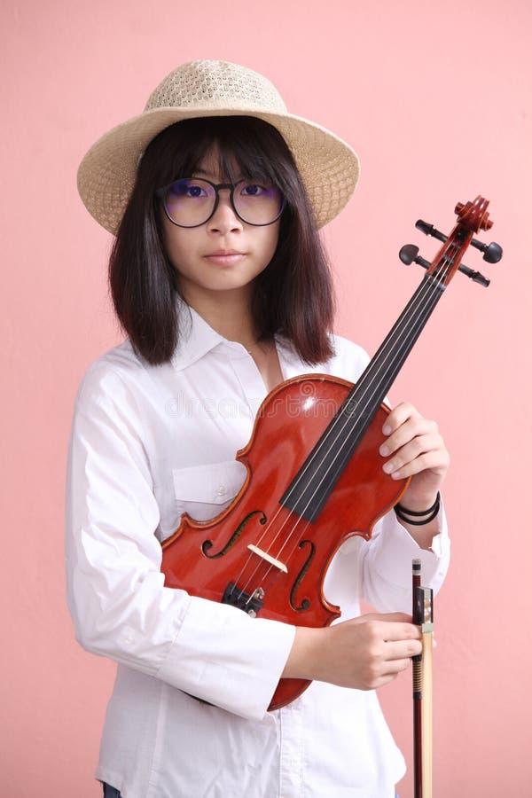 Азиатское предназначенное для подростков с улыбкой шляпы стекел скрипки стоковые фото