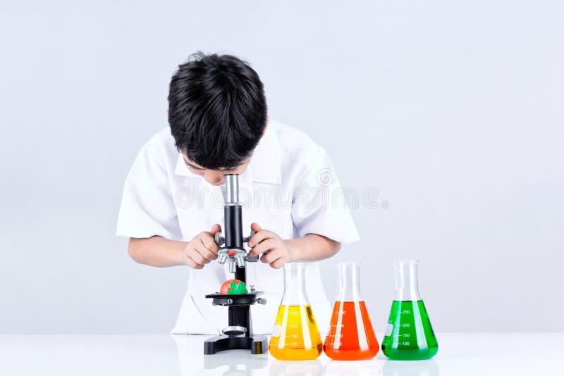 Азиатское проведение мальчика микроскоп эксперимента стоковая фотография rf
