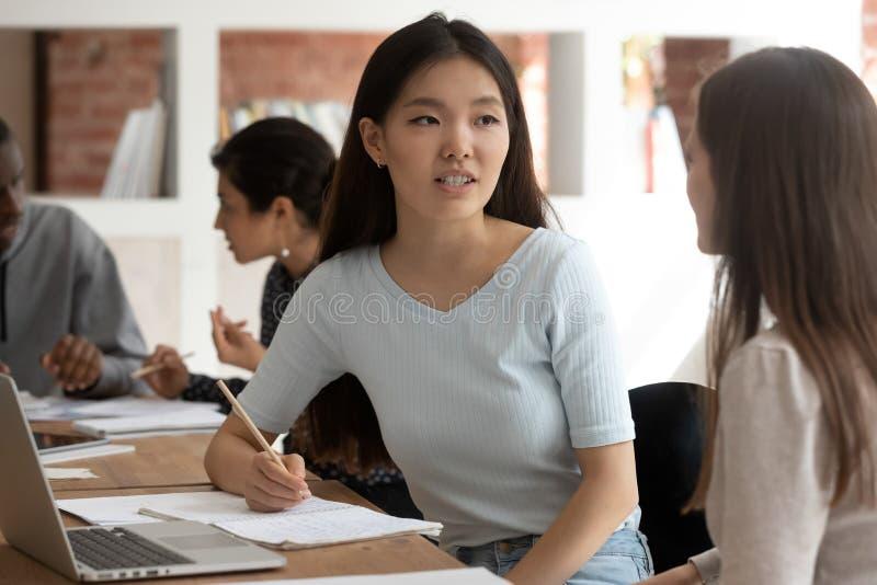 Азиатское разговаривать девушки с ответной частью подготавливая задачу в школе совместно стоковая фотография