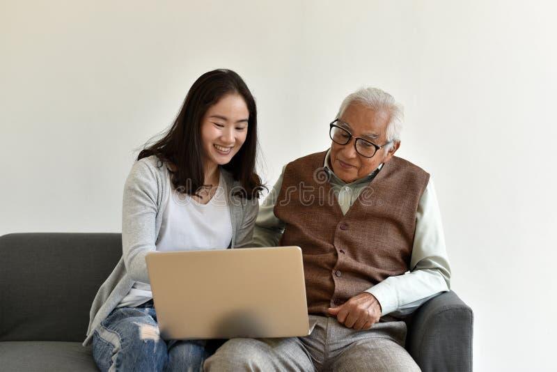Азиатское семейное отношение, дочь и пожилой отец используя ноутбук совместно стоковая фотография rf