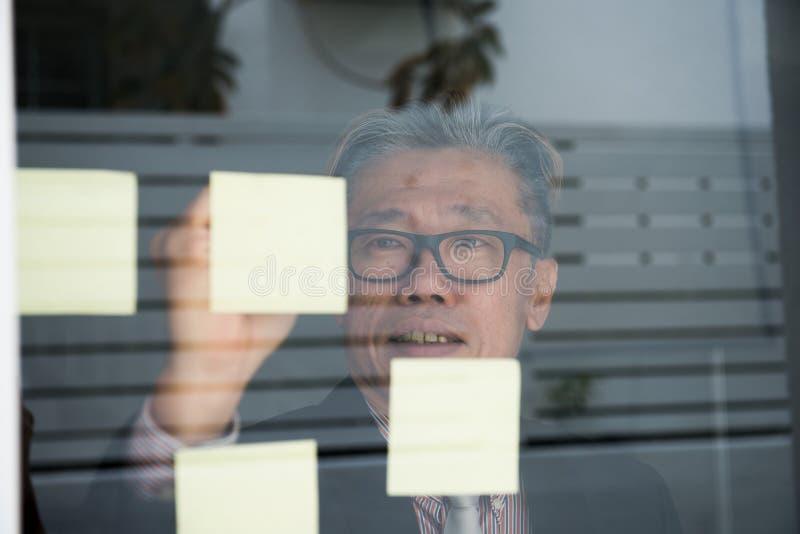 Азиатское сочинительство бизнесмена на стеклянной стене стоковые фотографии rf