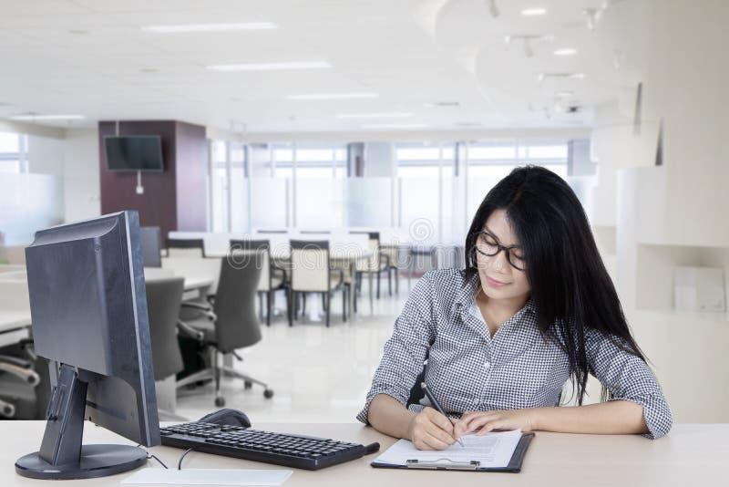 Азиатское сочинительство бизнес-леди на доске сзажимом для бумаги стоковая фотография