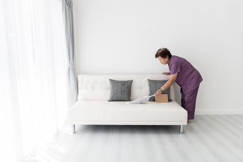 Азиатское старшее кресло чистки женщины дома стоковое фото rf