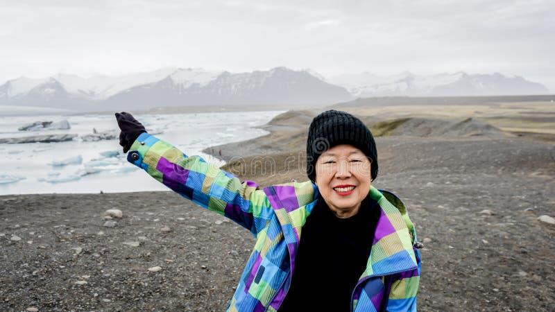 Азиатское старшее перемещение женщины к Исландии имеет выход на пенсию потехи стоковые изображения