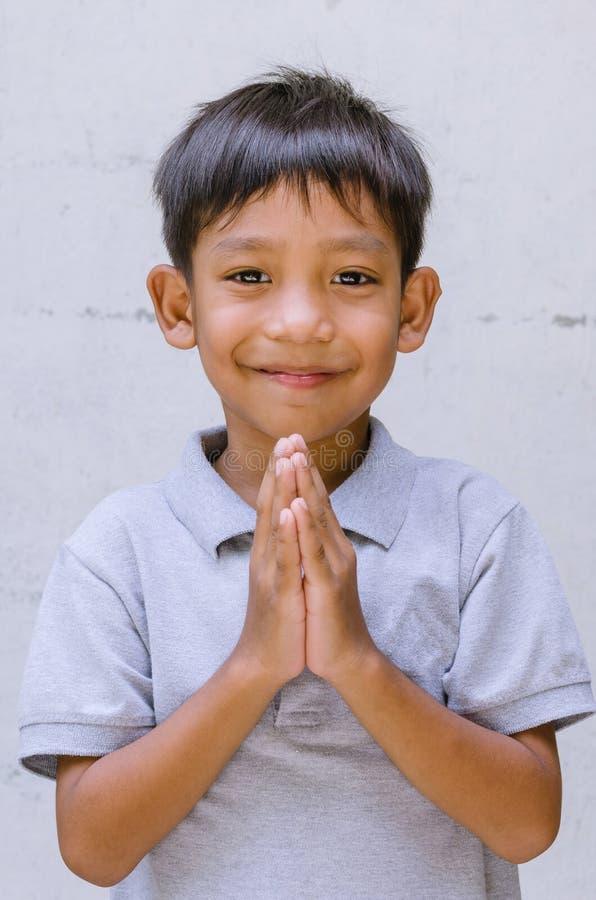 Азиатское уважение оплаты ребенка с его усмехаясь стоковые фотографии rf