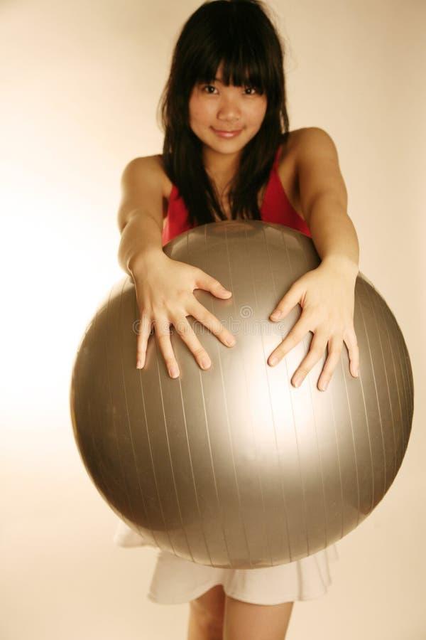 азиатское удерживание девушки тренировки шарика стоковые фото
