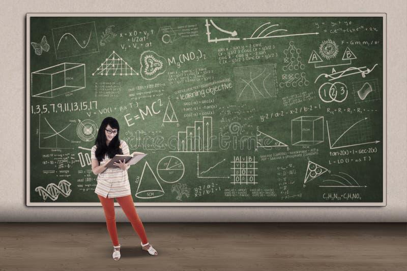 Азиатское чтение студентки на написанной доске в классе стоковое изображение