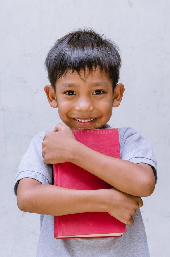 Азиатское чувство ребенка счастливое и обнять книгу стоковое изображение