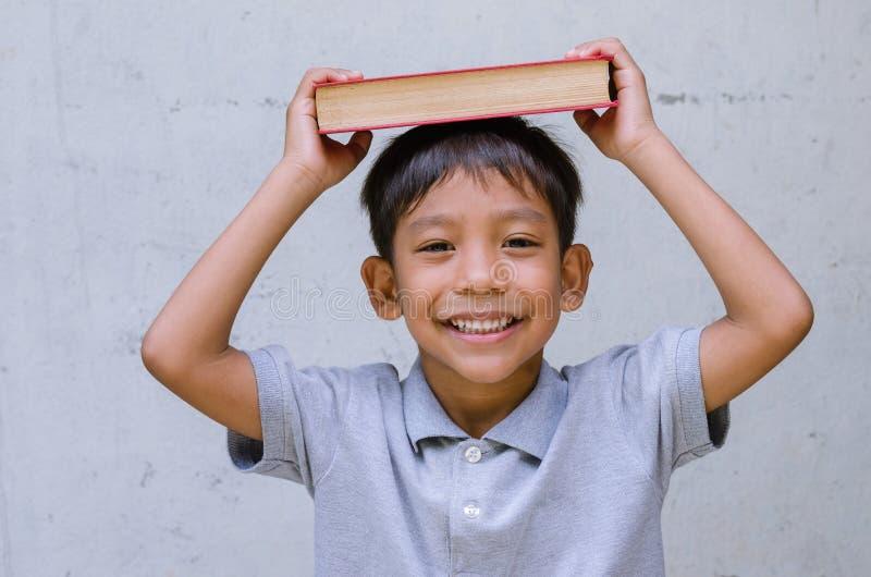Азиатское чувство ребенка счастливое с книгой стоковые фото