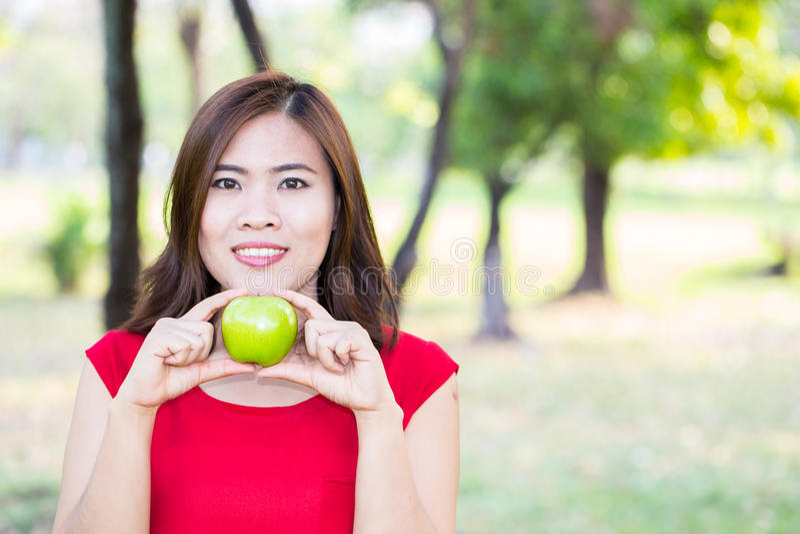 Азиатское яблоко выставки девушки с стороной улыбки, концепцией здоровой еды стоковая фотография