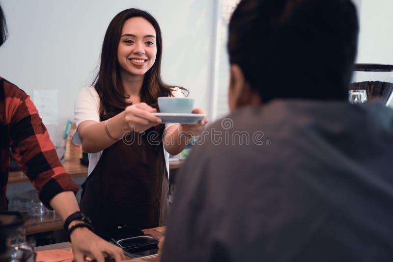 Азиатское barista служило чашка кофе в кафе к клиенту стоковая фотография rf