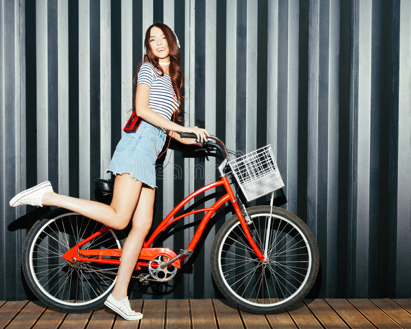 Азиат девушки Loker длинный шагающий в обмундировании лета, тапках, игроке кассеты и наушниках представляя и имея потеху с красны стоковое изображение
