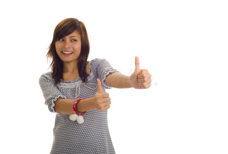 азиат thumbs 2 вверх по женщине стоковое фото