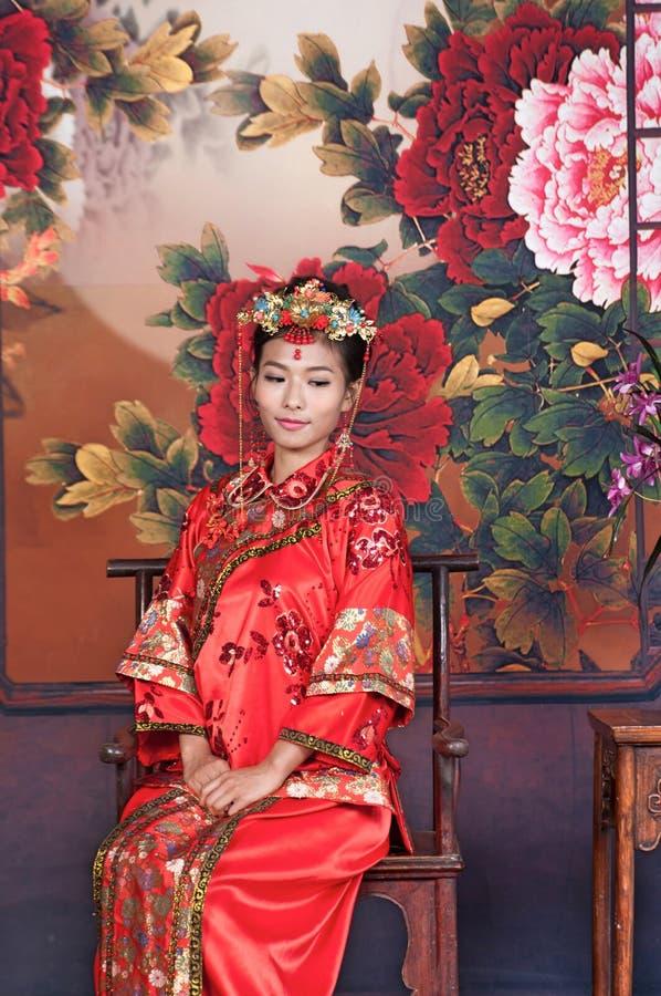 Азия/китайская девушка в красном традиционном платье стоковые изображения