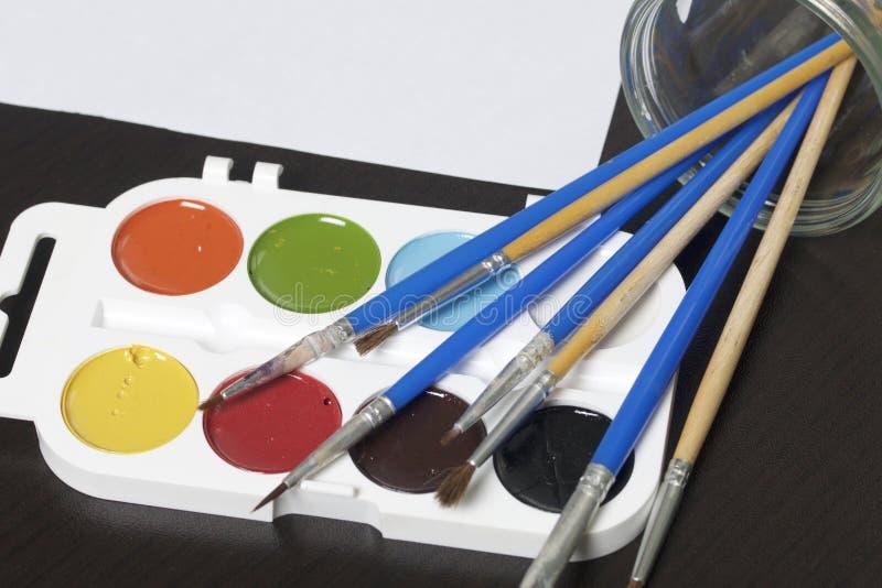Акварели и щетки на темной поверхности Рядом стекло для воды и рисовальной бумаги Вопросы для творческих способностей стоковая фотография rf