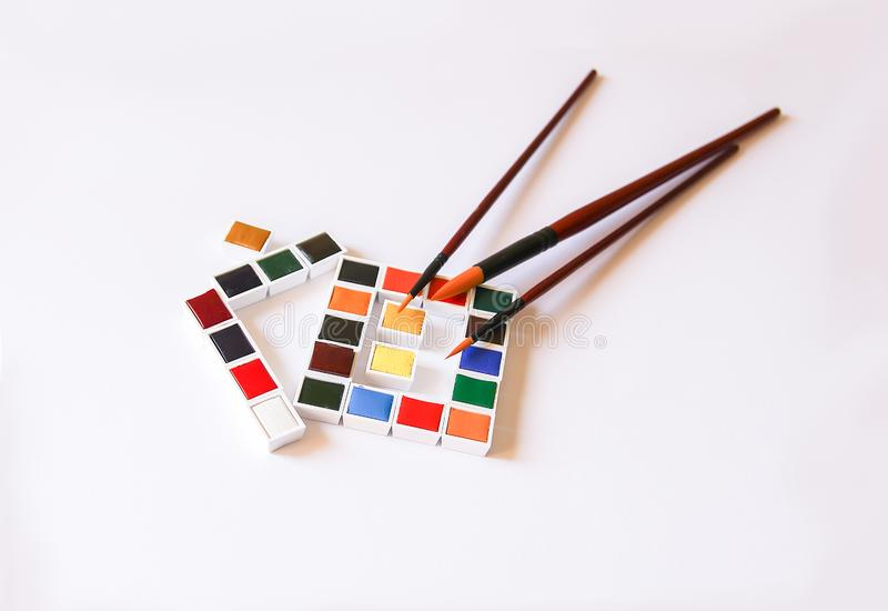 Акварель красит в форме дома и paintbrushes на белой предпосылке Крася инструменты o стоковое изображение rf