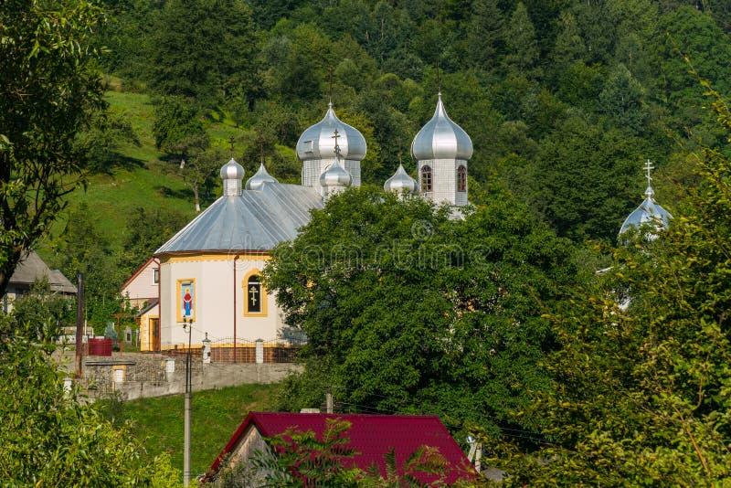 Аккуратная церковь с белыми стенами и сияющими куполами в солнце Размещенный в живописной сельской местности между красивым стоковое изображение