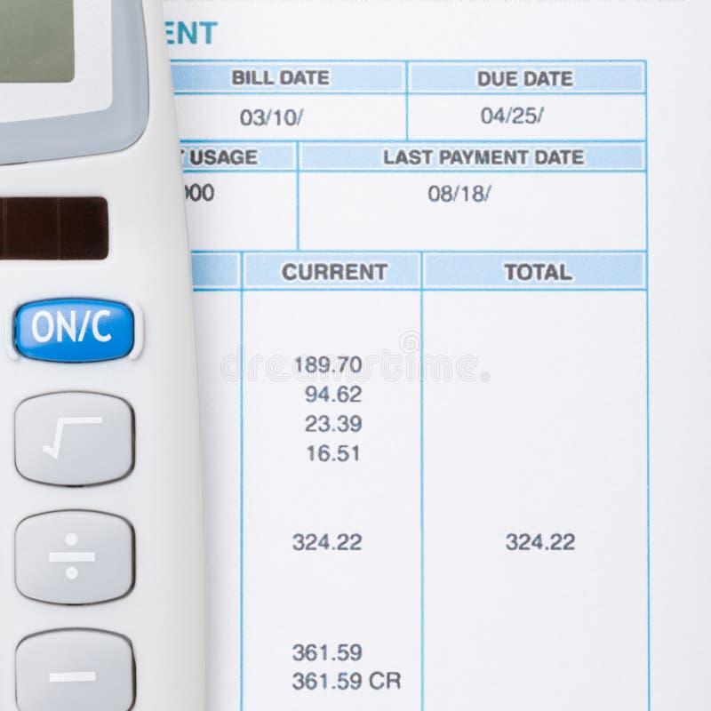 Аккуратные калькулятор и счета за коммунальные услуги рядом с ним - близкая поднимающая вверх съемка стоковые изображения