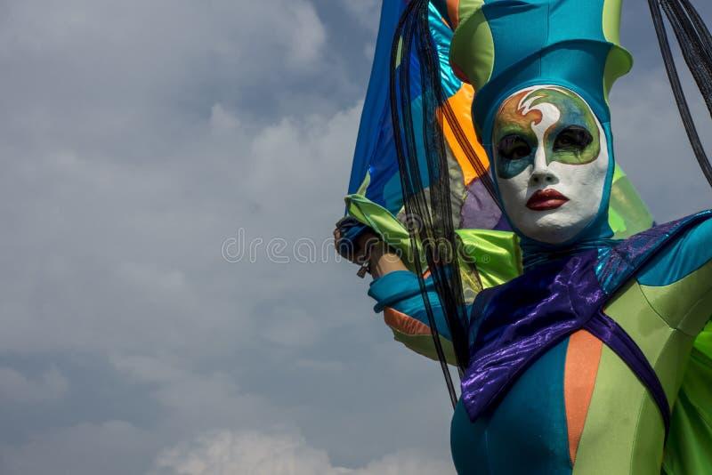 Акробат в красочной маске в голубом небе стоковая фотография rf