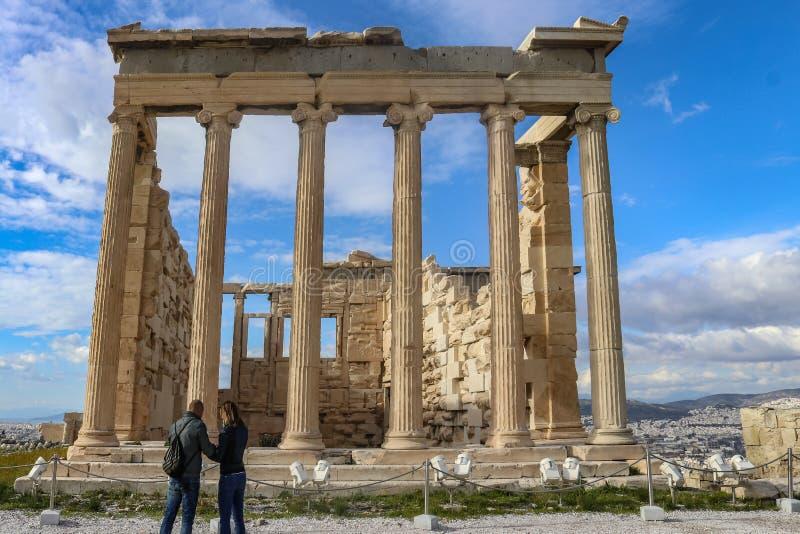 Акрополь Афина Греция виска Erechtheion с 2 туристами во фронте и крышах Афина и красивым небом в стоковые изображения