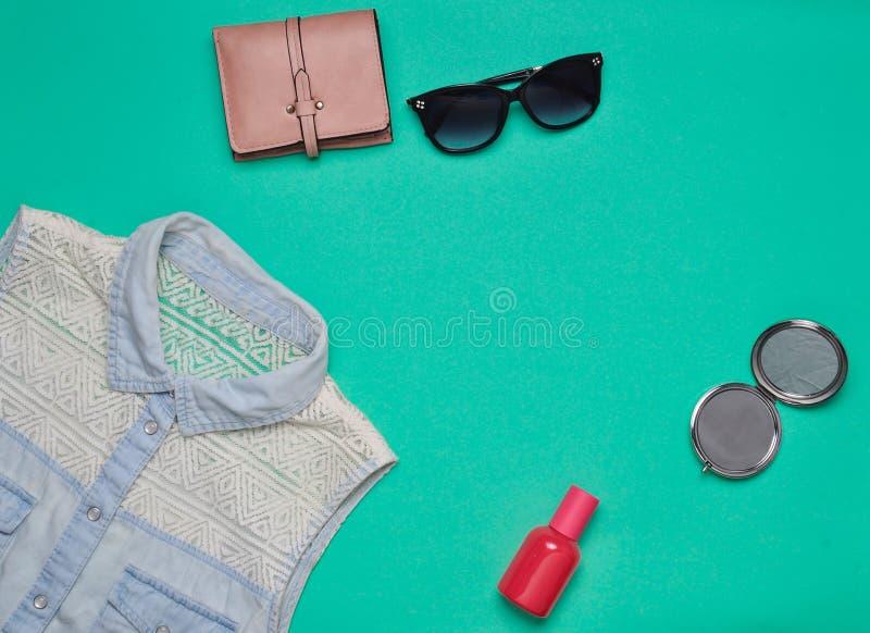 Аксессуары и одежда женщин на предпосылке бирюзы Джинсы рубашка, зеркало, флакон духов, солнечные очки, портмоне скопируйте космо стоковое фото