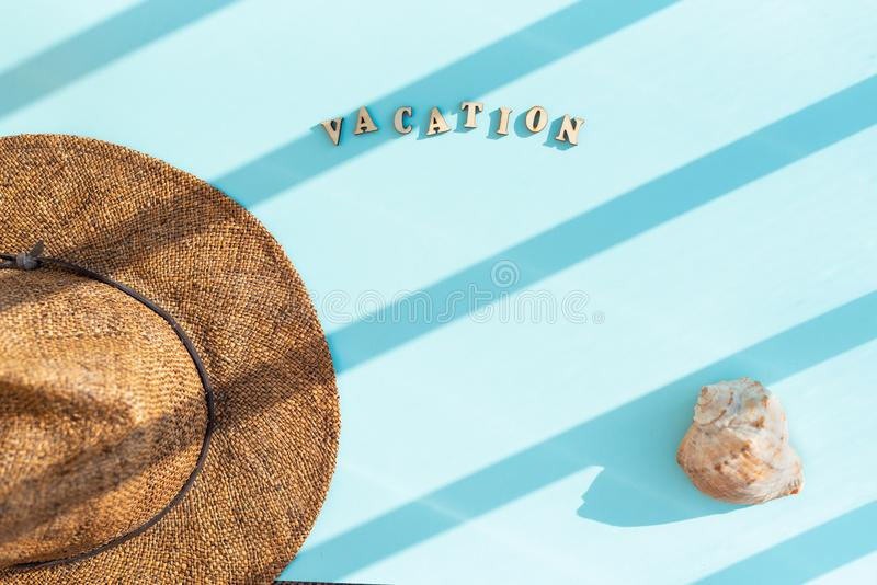 Аксессуары лета, шляпа, раковина, с каникулами слова в письмах на голубой предпосылке Трудный свет в нашивках r стоковое изображение