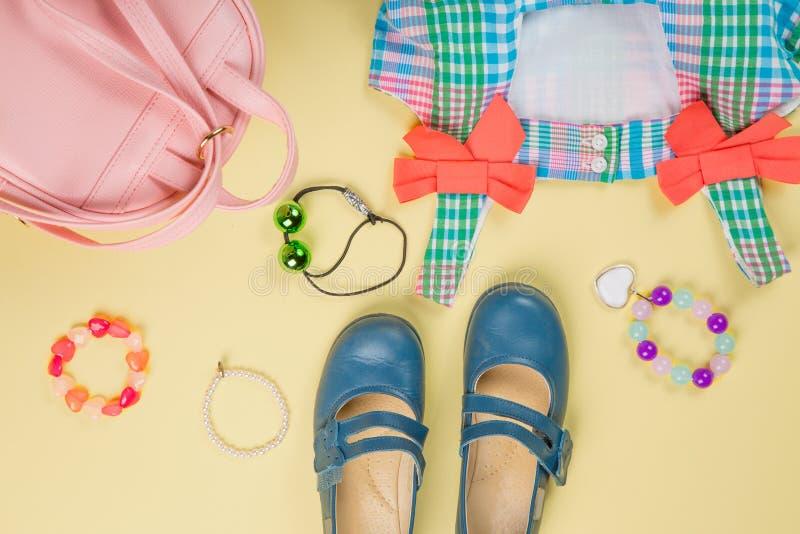Аксессуары маленькой девочки Розовая сумка с красочными платьем, circlet, связями волос и ботинками на желтой desaturated предпос стоковое фото rf