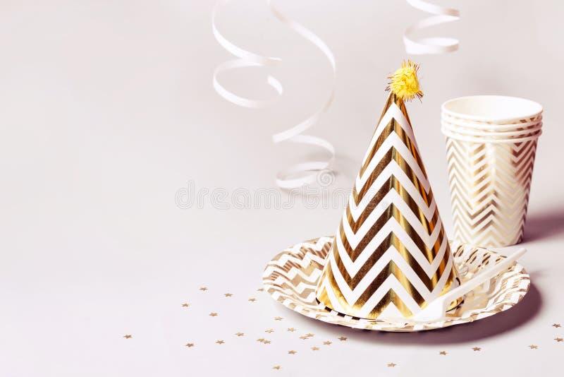 Аксессуары партии в золоте Бумажные блюда и confetti на серой предпосылке стоковые изображения